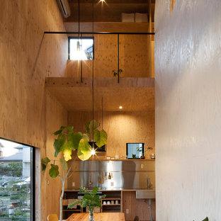 Idee per una piccola sala da pranzo aperta verso la cucina minimal con pavimento in compensato