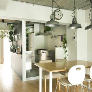 Ispirazione per una sala da pranzo aperta verso la cucina industriale con pareti bianche e parquet chiaro