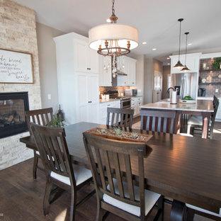 На фото: кухня-столовая среднего размера с бежевыми стенами, полом из винила, стандартным камином, фасадом камина из каменной кладки и коричневым полом с
