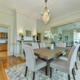 Imagen de comedor clásico, grande, cerrado, con paredes beige, suelo de madera en tonos medios, chimenea tradicional, marco de chimenea de hormigón y suelo marrón