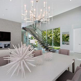 Diseño de comedor minimalista, de tamaño medio, abierto, con paredes grises, suelo de baldosas de porcelana, chimenea de doble cara, marco de chimenea de hormigón y suelo gris