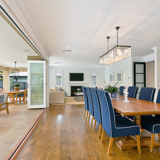 Photo of a large classic open plan dining room in Sydney with white walls, medium hardwood flooring, a standard fireplace and a wooden fireplace surround.
