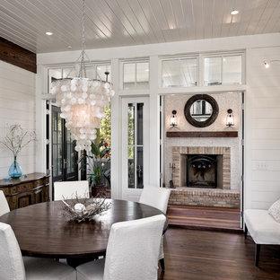 Modelo de comedor clásico con paredes blancas, suelo de madera oscura y marco de chimenea de ladrillo