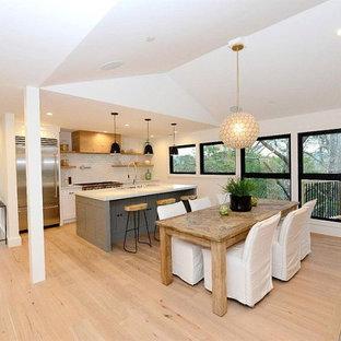 Idée de décoration pour une grand salle à manger ouverte sur la cuisine champêtre avec un mur blanc, un sol en bois clair, une cheminée double-face, un manteau de cheminée en lambris de bois et un sol marron.
