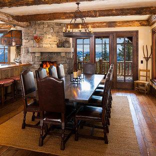 Foto di una grande sala da pranzo stile rurale con camino ad angolo e cornice del camino in pietra