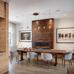 Modern inredning av en stor matplats med öppen planlösning, med vita väggar, mellanmörkt trägolv, en bred öppen spis och en spiselkrans i metall