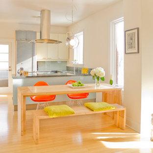 Idee per una sala da pranzo aperta verso la cucina minimal di medie dimensioni con pareti bianche e pavimento in bambù