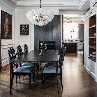 Inredning av en klassisk matplats, med vita väggar, mellanmörkt trägolv, en standard öppen spis, en spiselkrans i metall och brunt golv