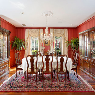 Enclosed dining room - mid-sized traditional medium tone wood floor and brown floor enclosed dining room idea in Other with red walls and no fireplace