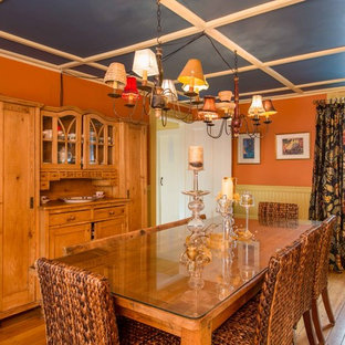 Mid-sized country medium tone wood floor enclosed dining room photo in Boston with orange walls and no fireplace