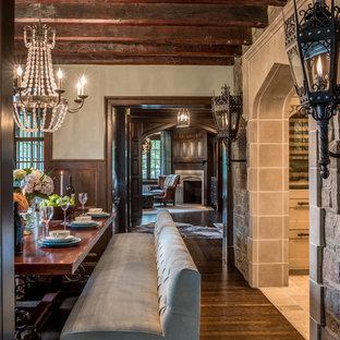 Immagine di una sala da pranzo tradizionale chiusa e di medie dimensioni con parquet scuro, camino ad angolo, cornice del camino in pietra e pareti bianche