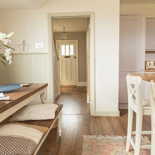 Immagine di una piccola sala da pranzo aperta verso la cucina country con pareti beige, pavimento in laminato, nessun camino e pavimento marrone