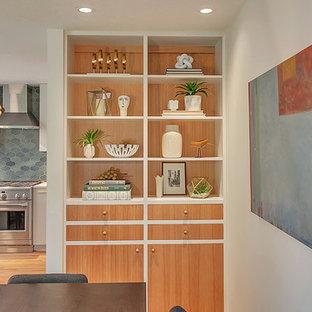 Diseño de comedor retro, de tamaño medio, abierto, con paredes grises, suelo de madera clara, chimenea de esquina y marco de chimenea de ladrillo