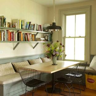 Immagine di una sala da pranzo country con pavimento in legno massello medio, camino classico, cornice del camino in legno e pareti beige
