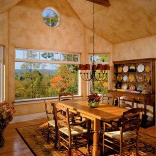 Example of a classic medium tone wood floor dining room design in New York with orange walls