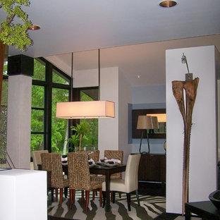 Immagine di un'ampia sala da pranzo aperta verso il soggiorno bohémian con pareti bianche, pavimento nero e pavimento in bambù