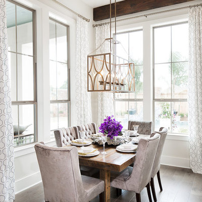 Example of a mid-sized transitional medium tone wood floor dining room design in New Orleans with white walls