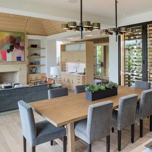 Immagine di un'ampia sala da pranzo aperta verso il soggiorno minimalista con pareti bianche, parquet chiaro, camino classico e cornice del camino in pietra