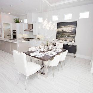 Modelo de comedor de cocina minimalista, grande, con paredes blancas y suelo de mármol