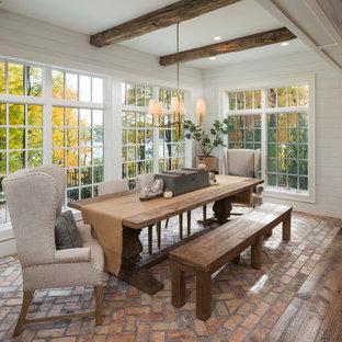 Aménagement d'une salle à manger ouverte sur la cuisine éclectique avec un sol en brique, un sol rouge et un mur blanc.