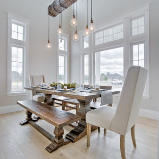 Inspiration for a farmhouse light wood floor and beige floor dining room remodel in Other with white walls