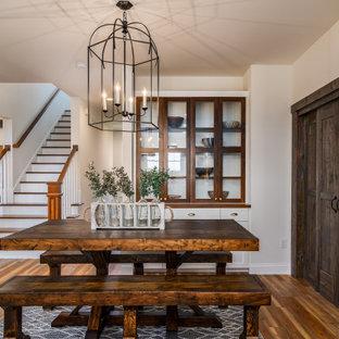 Landhaus Wohnküche ohne Kamin mit beiger Wandfarbe, braunem Holzboden, braunem Boden und freigelegten Dachbalken in Sonstige