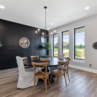 Immagine di una sala da pranzo country chiusa e di medie dimensioni con pareti grigie, pavimento in legno massello medio, pavimento marrone e pareti in perlinato