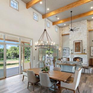 Cette photo montre une grand salle à manger ouverte sur la cuisine nature avec un mur gris, un sol en bois clair, une cheminée standard, un manteau de cheminée en pierre, un sol gris et un plafond en bois.