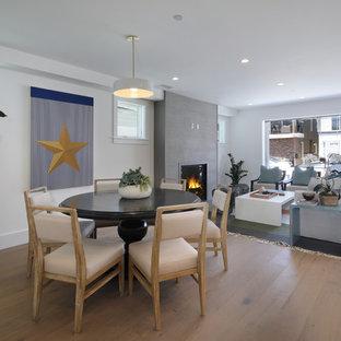 Foto de comedor costero, de tamaño medio, abierto, con paredes blancas, suelo de madera en tonos medios, chimenea tradicional, marco de chimenea de hormigón y suelo marrón
