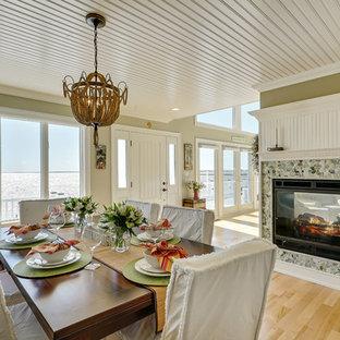 ニューヨークの大きいビーチスタイルのおしゃれなダイニングキッチン (ベージュの壁、淡色無垢フローリング、両方向型暖炉、石材の暖炉まわり) の写真