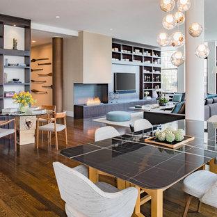 Foto de comedor actual, grande, abierto, con paredes blancas, suelo de madera en tonos medios, chimenea de esquina, marco de chimenea de metal y suelo marrón
