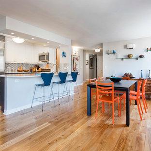 Immagine di una sala da pranzo aperta verso il soggiorno moderna di medie dimensioni con pareti bianche, parquet chiaro e nessun camino