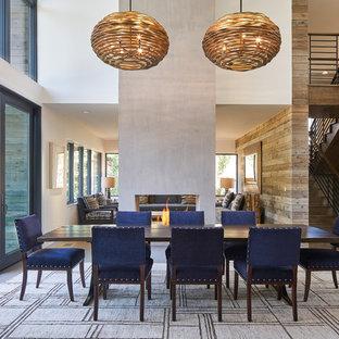 Immagine di una sala da pranzo aperta verso il soggiorno contemporanea di medie dimensioni con pareti beige, parquet scuro, camino bifacciale, cornice del camino in intonaco e pavimento marrone
