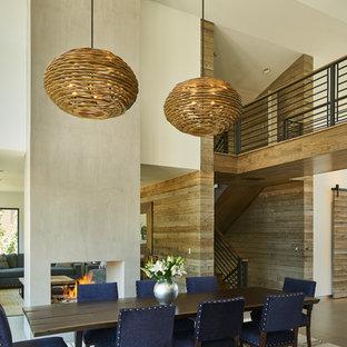 Foto de comedor contemporáneo, de tamaño medio, abierto, con paredes beige, suelo de madera oscura, chimenea de doble cara, marco de chimenea de yeso y suelo marrón