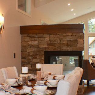 Diseño de comedor de cocina clásico, de tamaño medio, con paredes blancas, suelo de madera en tonos medios, chimenea de doble cara, marco de chimenea de piedra y suelo marrón