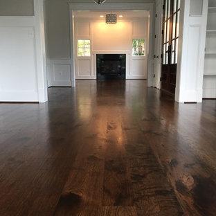 Immagine di un'ampia sala da pranzo aperta verso il soggiorno stile rurale con pareti beige, parquet scuro, cornice del camino in legno, nessun camino e pavimento marrone