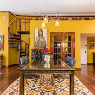 Esempio di un'ampia sala da pranzo aperta verso il soggiorno bohémian con pareti gialle, parquet scuro e nessun camino