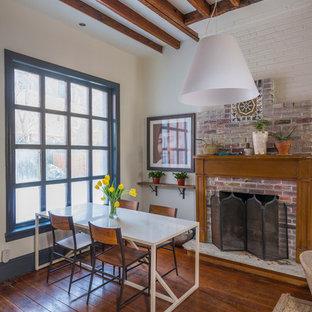 Ejemplo de comedor bohemio, grande, abierto, con marco de chimenea de ladrillo, paredes blancas, suelo de madera oscura, chimenea tradicional y suelo marrón