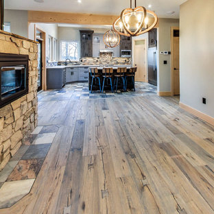 Ejemplo de comedor de cocina de estilo americano, de tamaño medio, con paredes beige, suelo de madera clara, chimenea de doble cara y marco de chimenea de piedra