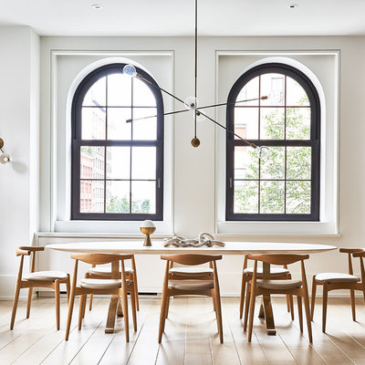 Inspiration for a scandinavian light wood floor and beige floor great room remodel in New York with white walls and no fireplace
