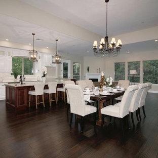 Foto di un'ampia sala da pranzo aperta verso la cucina contemporanea con pareti beige, parquet scuro, camino sospeso, cornice del camino in intonaco e pavimento marrone