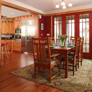 Immagine di una sala da pranzo aperta verso la cucina american style con pareti rosse e parquet scuro