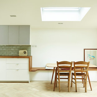 This is an example of a contemporary kitchen/dining room in London with white walls and light hardwood flooring.