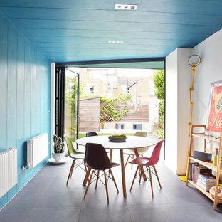 Esempio di una sala da pranzo minimal chiusa e di medie dimensioni con pareti blu, nessun camino e pavimento grigio