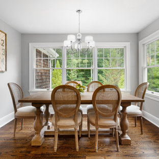 Example of a mid-sized transitional medium tone wood floor and brown floor enclosed dining room design in New York with gray walls