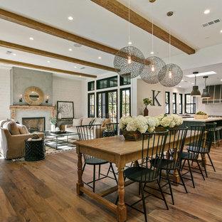 Immagine di una sala da pranzo aperta verso il soggiorno classica con pareti bianche, pavimento in legno massello medio e nessun camino