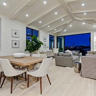 Diseño de comedor actual, de tamaño medio, abierto, con paredes blancas, suelo de madera clara, chimenea lineal y marco de chimenea de hormigón