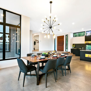 This is an example of a contemporary open plan dining in Sunshine Coast with white walls, concrete floors and grey floor.