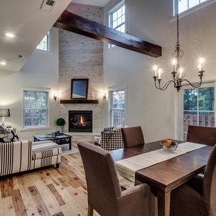 Imagen de comedor clásico renovado, abierto, con paredes blancas, suelo de madera clara, chimenea de esquina y marco de chimenea de piedra