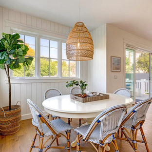 Réalisation d'une salle à manger ouverte sur le salon marine avec un mur blanc, un sol en bois brun, un sol marron et du lambris de bois.
